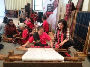 Salah seorang pengunjung Ulos Fest 2019, Hotma Uli Boru Sihite sedang memperhatikan Penenun Ulos Batak yang sedang memperlihatkan cara menenun Ulos. Ulos Fest 2019 digelar di Museum Nasional Indonesia, Jakarta Pusat, sejak tanggal 12-17 November 2019. Dibuka dan dihadiri Ketua MPR RI Bambang Soesatyo dan Gubernur Sumut Edhy Rahmayadi. Ulos Fest 2019 memamerkan beragam motif ulos dari 5 Puak Batak Raya, yakni Angkola atau Mandailing, Karo, Pakpak, Simalungun, dan Toba. Tersedia juga Bazar yang menjual berbagai macam Ulos Batak dan kreasi motif Ulos Batak berupa pakaian, tas, suvenir, dan lain-lain.